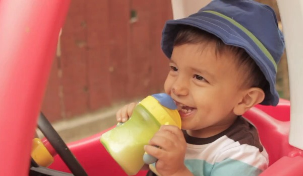 Cute kid drinking from a sippy cup