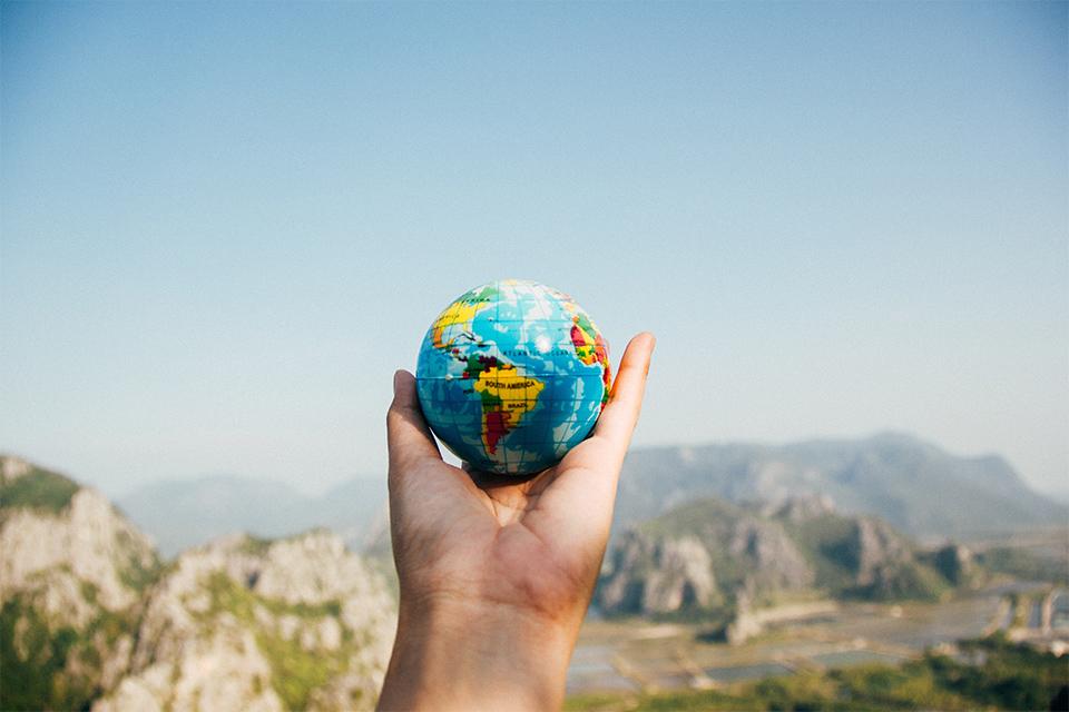 Person holding a tiny globe